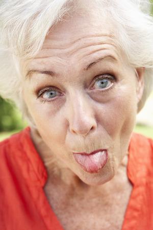頭と舌を突っつい年配の女性の肩の肖像画 写真素材