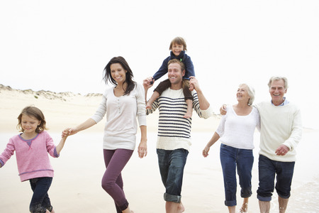 six month old: Multi Generation Family Walking Along Beach Together