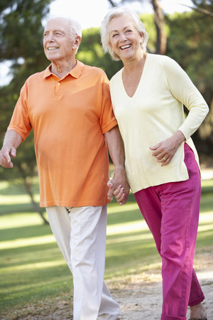 strolling: Senior Couple Walking In Park Together Stock Photo