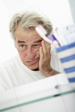 Hombre mayor cansado Mirando a la Reflexión En Espejo de baño Foto de archivo - 42254198