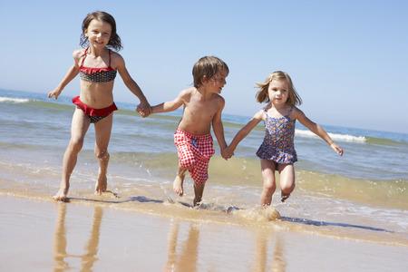 Niños que se ejecutan a lo largo de la playa