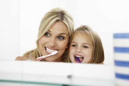 Moeder en dochter borstelen tanden op elkaar