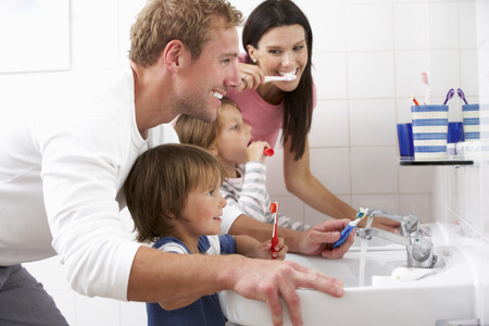 Family In Bathroom Brushing Teeth