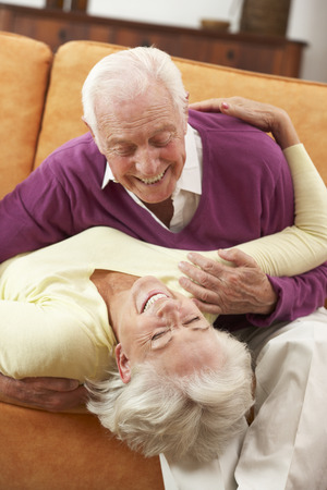 happy senior couple: Romantic Senior Couple Lying On Sofa At Home