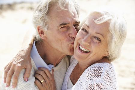 man woman kissing: Senior Couple Walking Along Beach Together