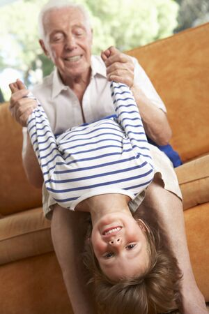 two year old: Grandfather And Grandson Having Fun On Sofa Stock Photo