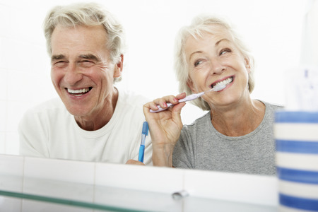 white teeth: Senior Couple In Bathroom Brushing Teeth