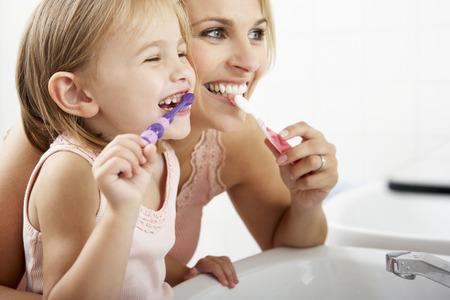 kinderschoenen: Moeder en dochter borstelen tanden op elkaar