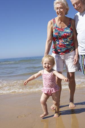 senior women: Grandparents And Granddaughter Walking Along Beach