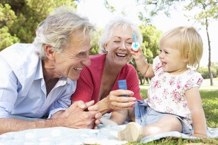 Prarodiče a vnučka hrát v parku Společně Reklamní fotografie