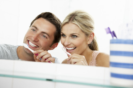 Couple In Bathroom Brushing Teeth