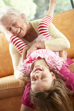 tickling: Grandmother And Granddaughter Having Fun On Sofa