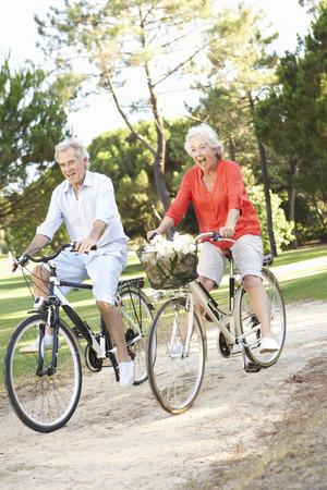 andando en bicicleta: Pares mayores que disfrutan paseo del ciclo Foto de archivo
