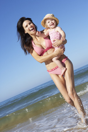 mum: Mother With Young Daughter Running Along Beach Together