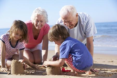 조부모와 손자들이 해변에서 샌드캐슬을 짓다.