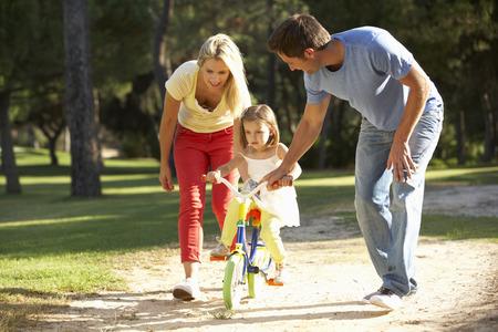 niños en bicicleta: Los padres que enseñan Hija A Ride Bike Foto de archivo