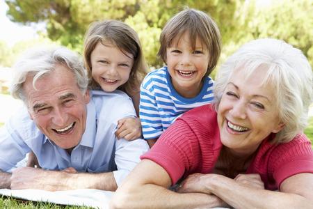 riendo: Abuelos y nietos en parque junto