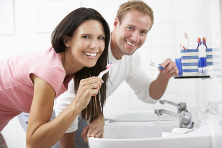 teeth cleaning: Couple In Bathroom Brushing Teeth