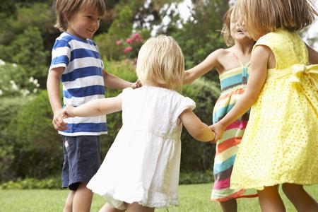 Gruppe der Kinder spielen im Freien zusammen Standard-Bild