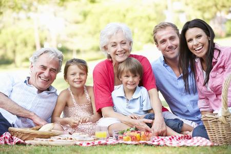 familias felices: Multi generacional disfrutan de comida campestre Juntos