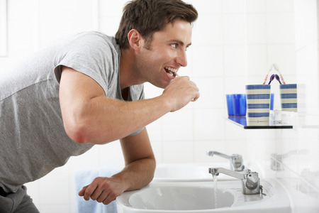 teeth cleaning: Man In Bathroom Brushing Teeth