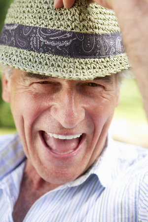 one person: Head And Shoulders Portrait Of Smiling Senior Man With Sun Hat