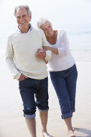 一緒にビーチに沿って歩くシニア カップル 写真素材