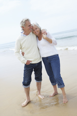 ancianos caminando: Senior pareja caminando por la playa juntos