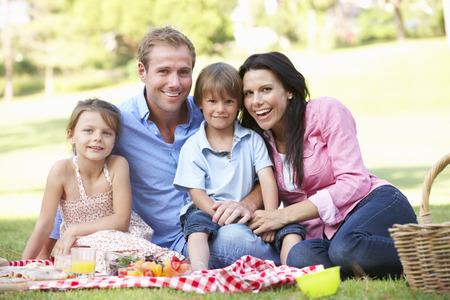 familia pic nic: Familia que disfruta de la comida campestre Juntos