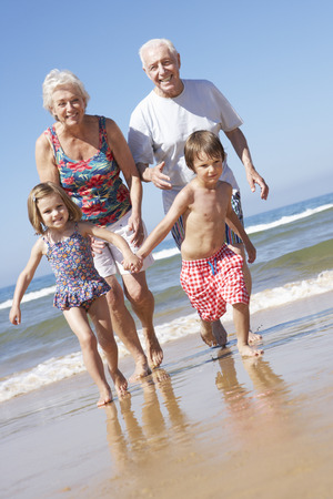 Grandparents And Grandchildren Running Along Beach
