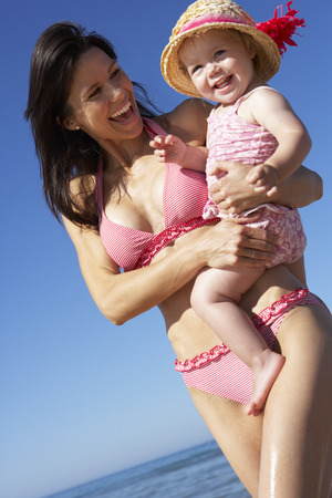 parent with child: Mother With Young Daughter Running Along Beach Together