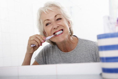 teeth cleaning: Senior Woman In Bathroom Brushing Teeth