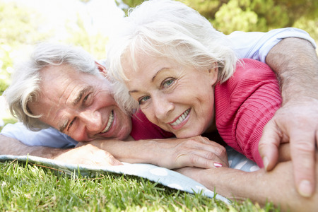 couples outdoors: Senior Couple Relaxing In Park Together Stock Photo