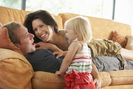 Familie liggend op de bank thuis Stockfoto