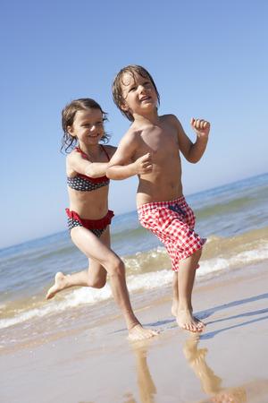 ni�o corriendo: Ni�os que se ejecutan a lo largo de la playa