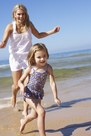 old girl: Mother Chasing Daughter Along Beach Stock Photo