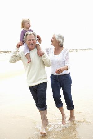 abuelos: Abuelos y nieta caminando por la playa juntos Foto de archivo
