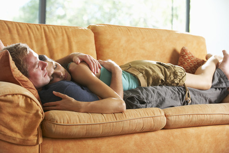 couple on couch: Romantic Couple Lying On Sofa At Home