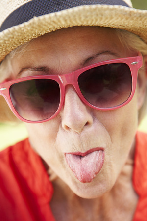 female tongue: Head And Shoulders Portrait Of Senior Woman Poking Out Tongue
