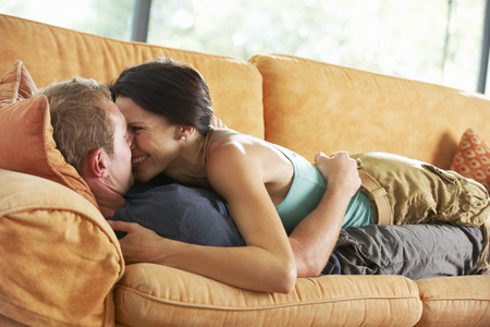 couple cuddling: Romantic Couple Lying On Sofa At Home