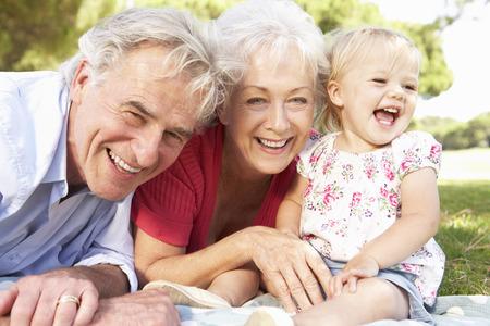 abuelos: Abuelos y nieta en parque junto