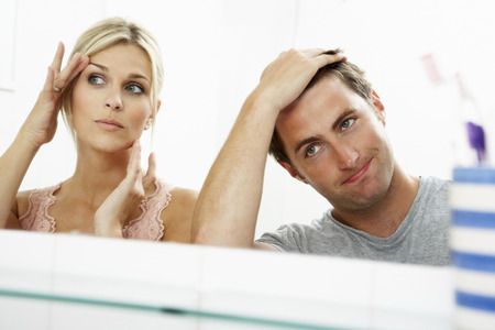 Couple Looking At Reflections In Mirror For Signs Of Ageing