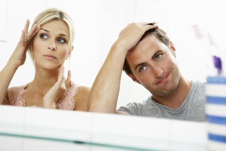 arrugas: Pareja Mirando a Reflexiones En Espejo para detectar signos de envejecimiento Foto de archivo
