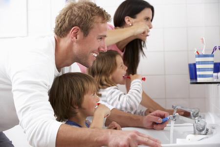 Family In Bathroom Brushing Teeth