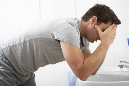 to sink: Tired Man In Standing At Bathroom Sink