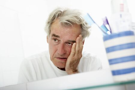 man looking out: Tired Senior Man Looking At Reflection In Bathroom Mirror
