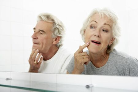 ageing: Senior Couple Looking At Reflections In Mirror For Signs Of Ageing Stock Photo