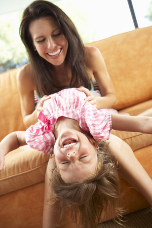 tickling: Mother And Daughter Having Fun On Sofa Stock Photo