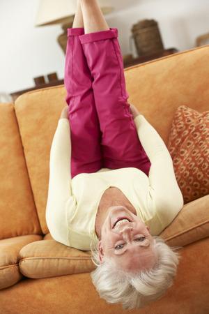 cabeza abajo: Mujer mayor que miente upside-down en el sofá en casa