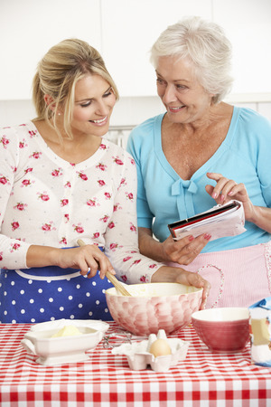 grown ups: Senior Woman And Adult Daughter Baking In Kitchen